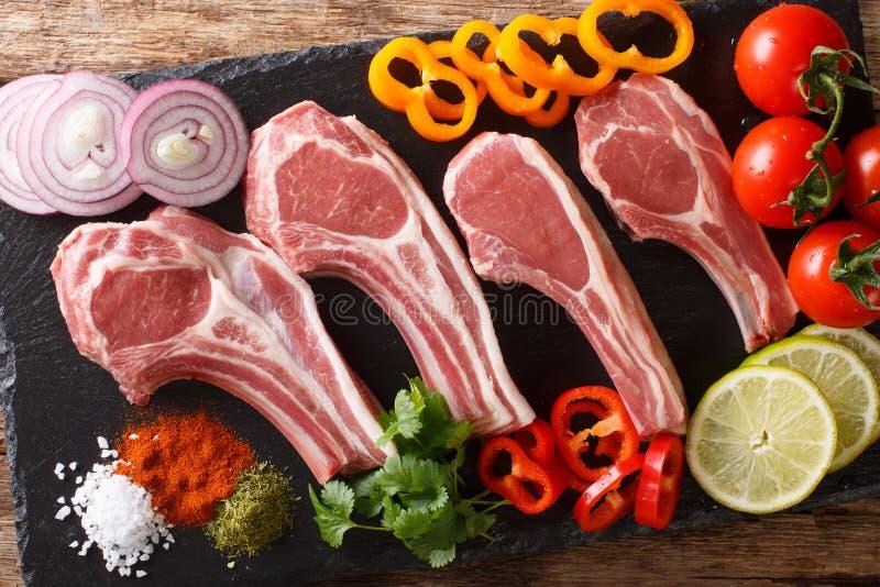 Tagli di agnello crudi freschi sull'osso con il primo piano di verdure degli ingredienti vista superiore orizzontale fotografia stock libera da diritti