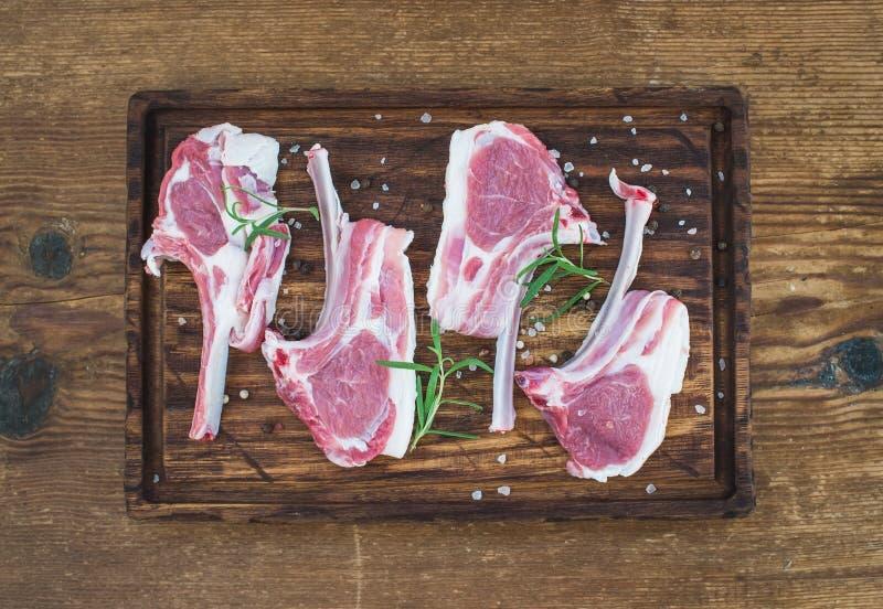 Tagli di agnello grezzi Carrè di agnello con i rosmarini e le spezie sul tagliere rustico sopra vecchio fondo di legno immagini stock