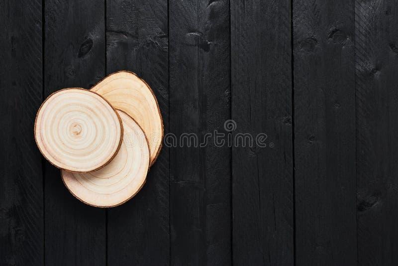Tagli di legno trasversali della sega sulla tavola di legno nera immagini stock
