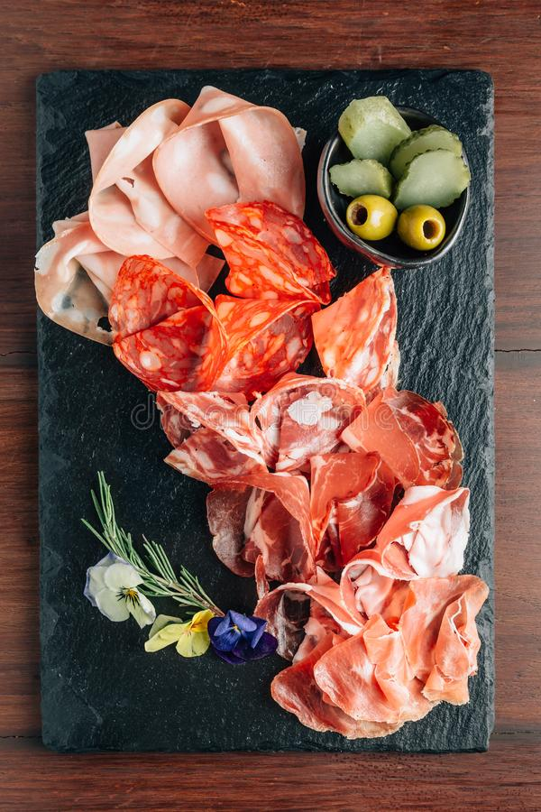 Tagli freddi sul piatto di pietra con il prosciutto di Parma, il bacon, il salame e le salsiccie decorati con i fiori su fondo di fotografia stock libera da diritti