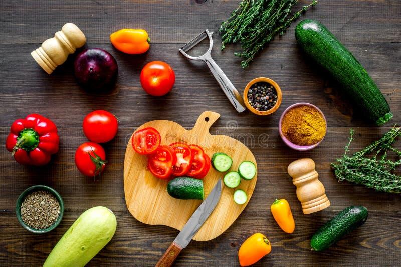 Tagli gli ortaggi freschi differenti sul tagliere per la cottura dello stufato di verdure Vista superiore del fondo di legno scur fotografie stock libere da diritti