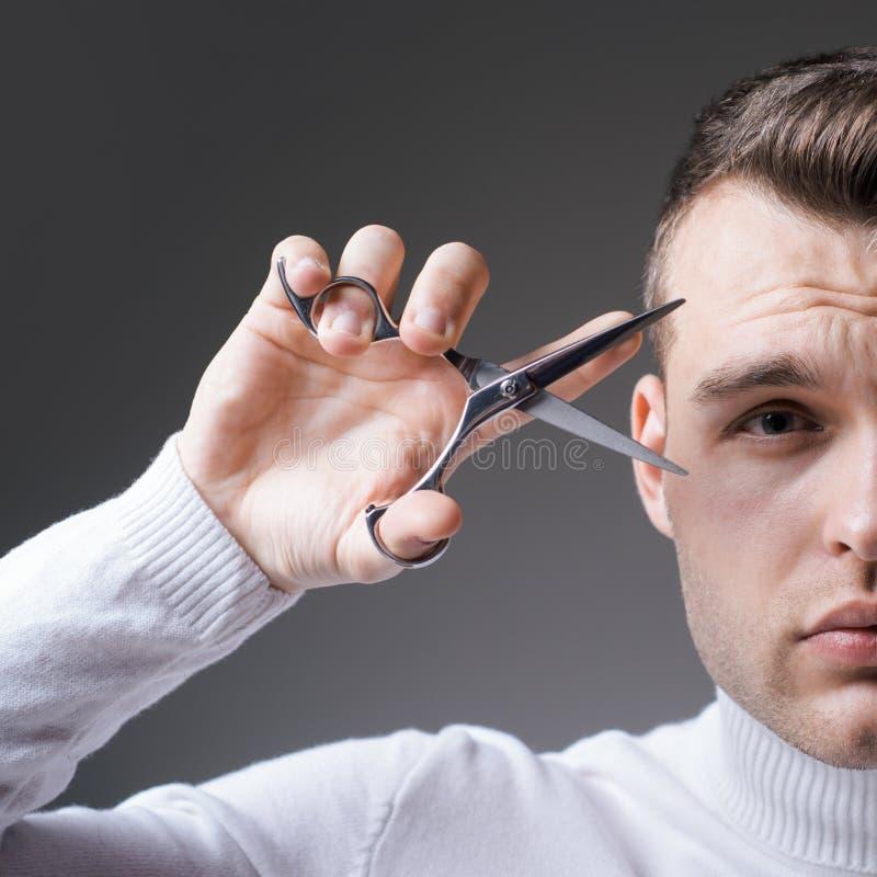 Tagli i capelli Forbici rigorose della tenuta del fronte dell'uomo Forbici d'acciaio della tenuta lucida dell'acconciatura del ba fotografia stock libera da diritti