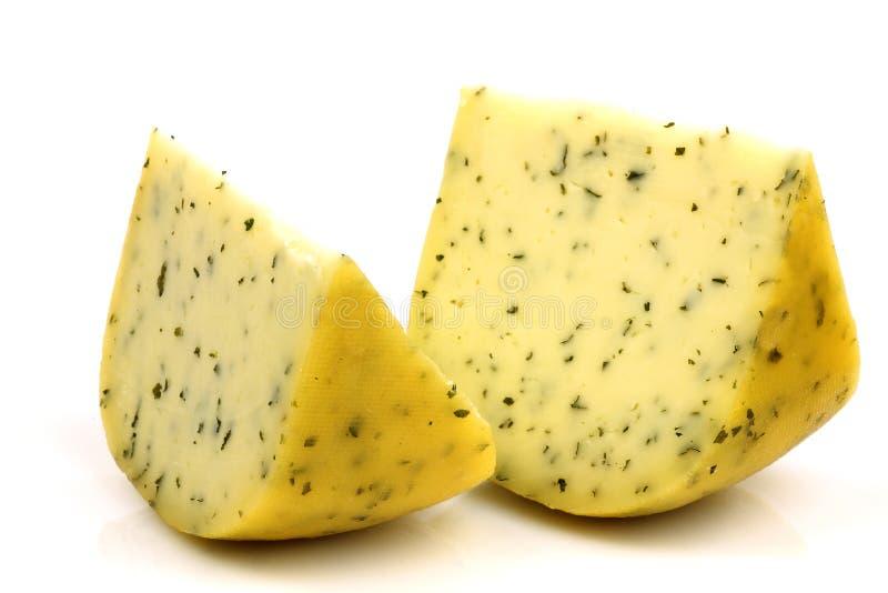 Tagli il formaggio Gouda tradizionale con le erbe immagine stock