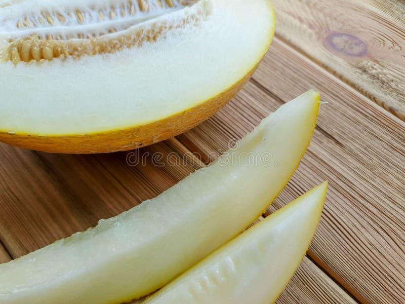 Tagli il melone e le fette del melone su fondo di legno marrone fotografia stock