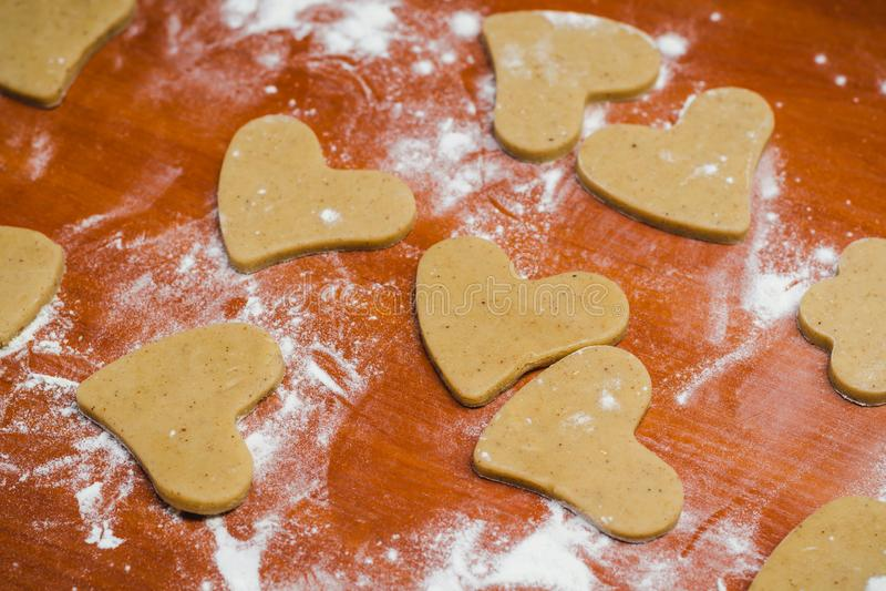 Tagli il pan di zenzero in una forma del cuore su una tavola di legno, versata con la farina di frumento fotografia stock