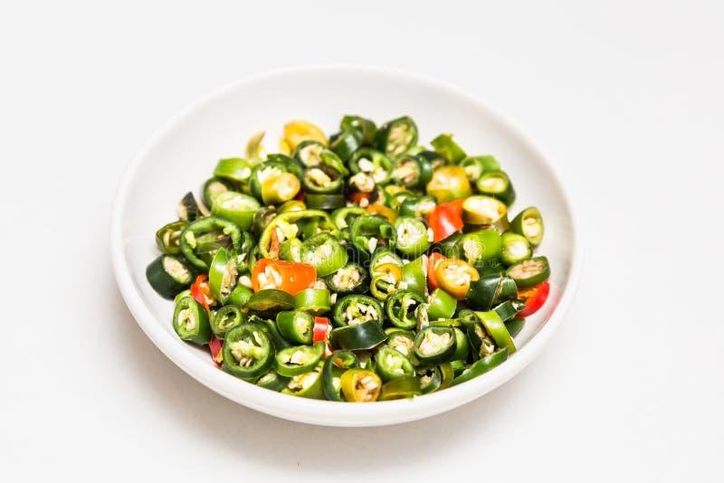Tagli il piccolo peperoncino rosso servito sul piatto della salsa fotografia stock