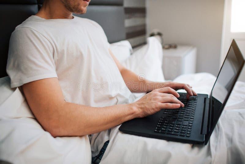 Tagli il punto di vista del giovane a letto questa mattina Lavora tenendo il computer portatile e scrivendo sulla tastiera Lavoro immagini stock libere da diritti