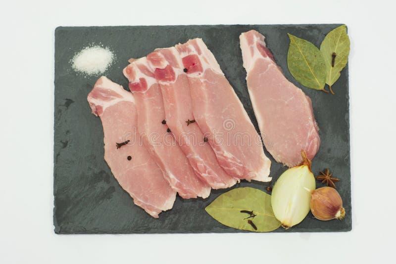 Tagli la carne e le spezie su un tagliere Bistecca, bacon, manzo fotografia stock libera da diritti