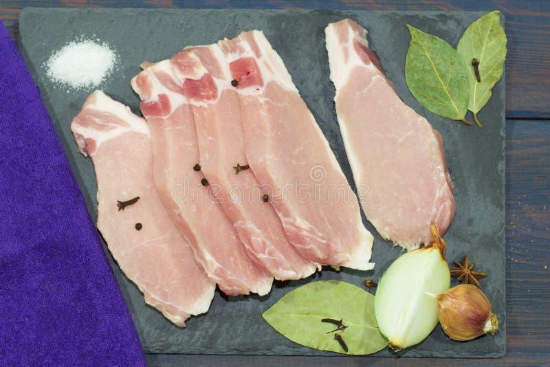 Tagli la carne e le spezie su un tagliere Bistecca, bacon, manzo fotografia stock