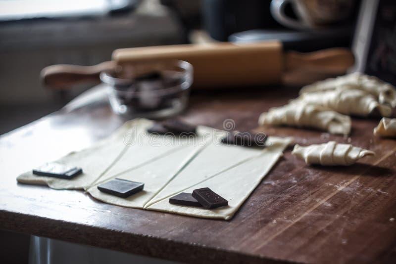 Tagli la pasta in triangoli per i croissant con cioccolato immagine stock libera da diritti