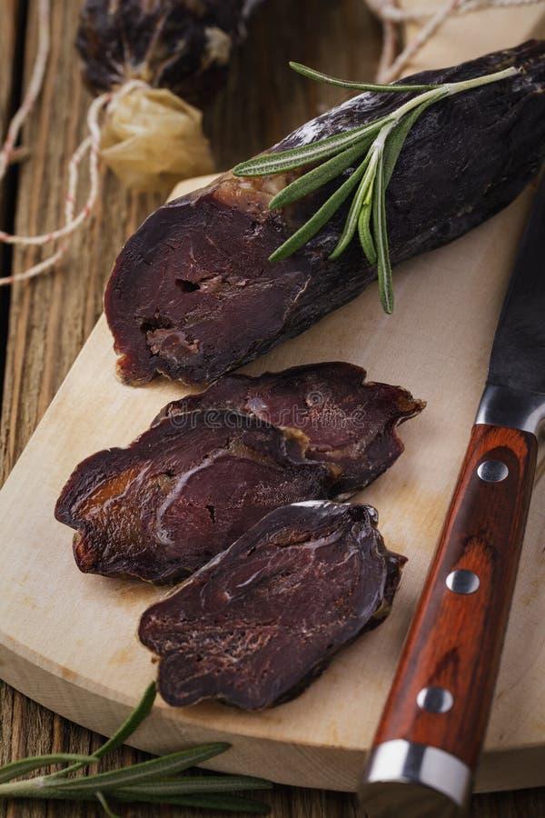 Tagli la salsiccia affumicata riscaldata sul posto su un tagliere immagine stock libera da diritti