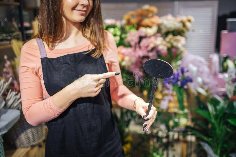 Tagli la vista del punto femminile del fiorista del oyung alla cosa di legno nera a disposizione Sta davanti ai fiori ed alle pia fotografia stock libera da diritti