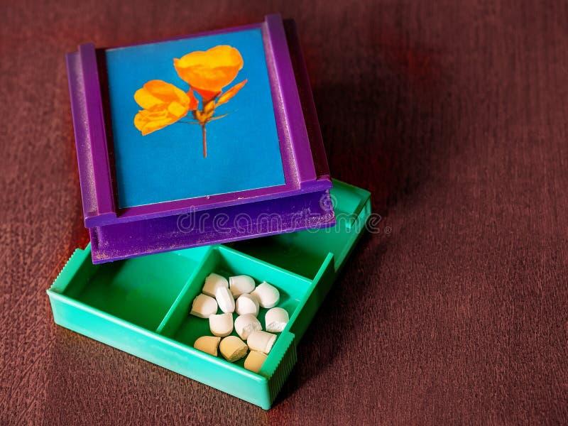 Tagli in mezze pillole nel contenitore della medicina immagini stock libere da diritti