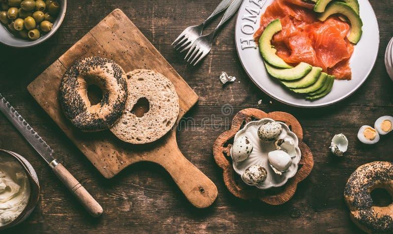 Tagli in mezzo panino del bagel sul bordo di sventramento di legno con gli ingredienti del coltello e del panino di pane: uova di fotografia stock libera da diritti