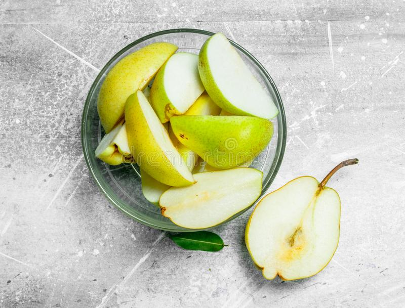 Tagli una pera in una ciotola di vetro fotografia stock libera da diritti