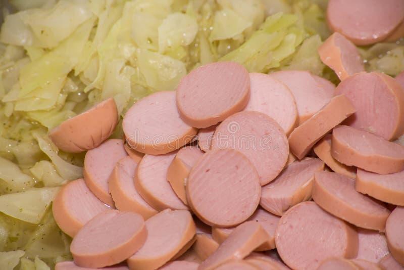 Tagliando le fette di salsicce di Francoforte del manzo stufi con cavolo bianco immagine stock