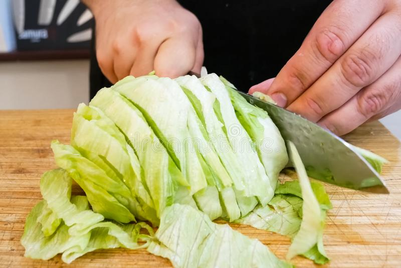 Tagliare i cavoli greggi su una tavola da taglio con un coltello Cavolo da cucina fotografia stock libera da diritti