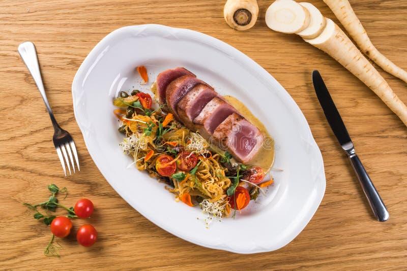 Tagliata tuńczyk z jarzynowym spaghetti Smażący tuńczyk z garnirunkiem na białym talerzu Zakąska talerz Rybiego naczynia włoszczy fotografia stock