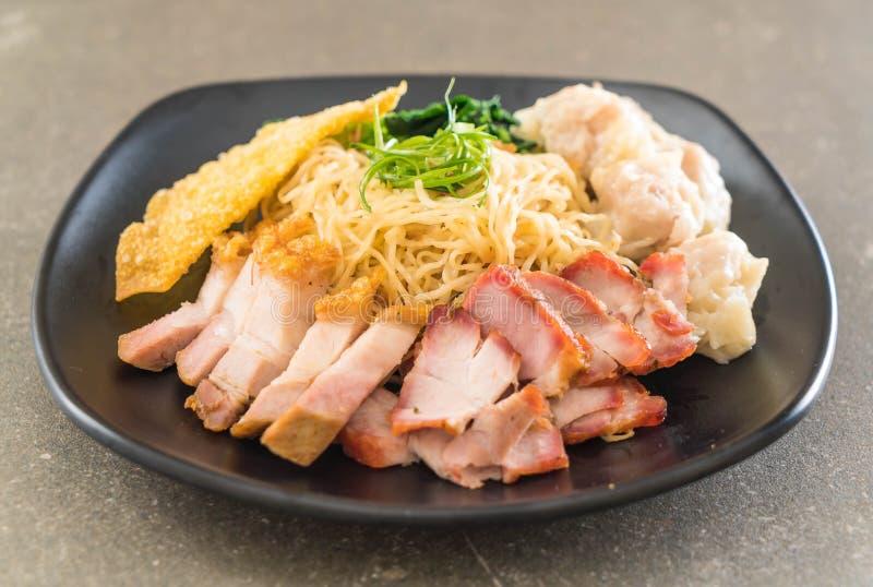 Tagliatella dell'uovo con l'arrosto di maiale rosso, la carne di maiale croccante, gli gnocchi e la minestra fotografia stock
