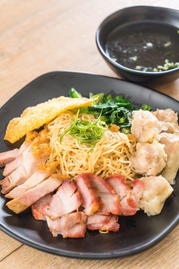 Tagliatella dell'uovo con l'arrosto di maiale rosso, la carne di maiale croccante, gli gnocchi e la minestra immagine stock