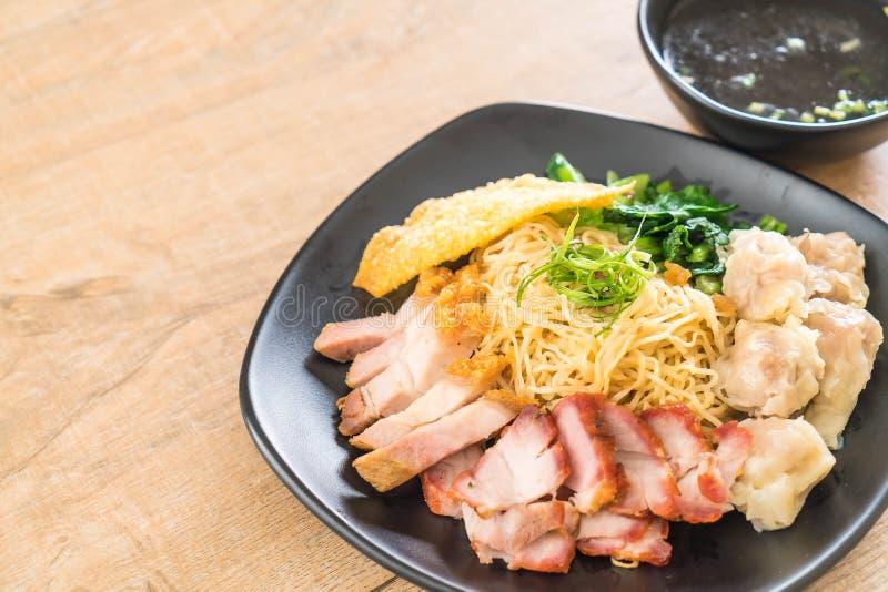 Tagliatella dell'uovo con l'arrosto di maiale rosso, la carne di maiale croccante, gli gnocchi e la minestra fotografia stock libera da diritti