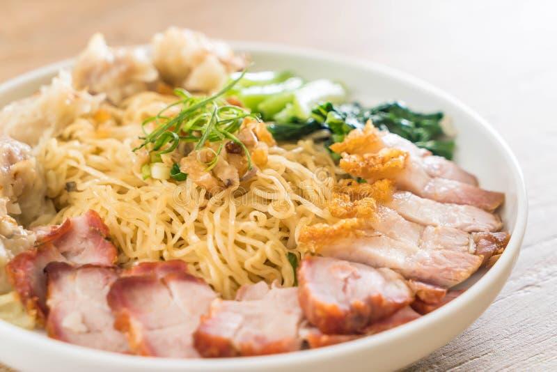 Tagliatella dell'uovo con l'arrosto di maiale rosso, la carne di maiale croccante, gli gnocchi e la minestra immagini stock libere da diritti