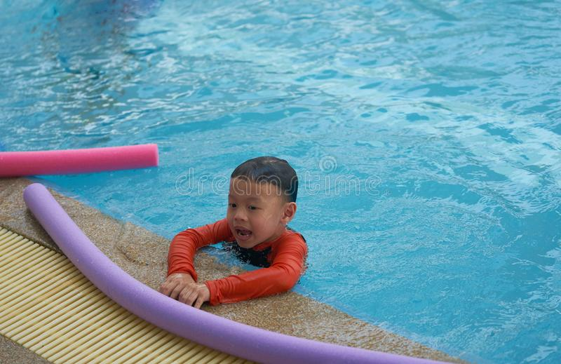 Tagliatella della schiuma di uso del ragazzo o del bambino per l'apprendimento del nuoto dal lato di wate immagine stock