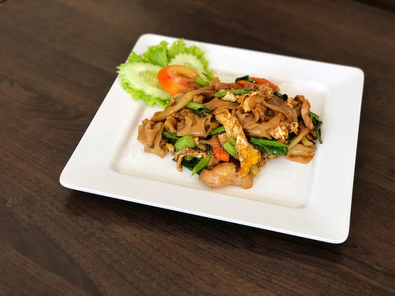 Tagliatella fritta con la salsa e carne di maiale di soia e verdura, pomodoro in piatto bianco sulla tavola nera fotografia stock