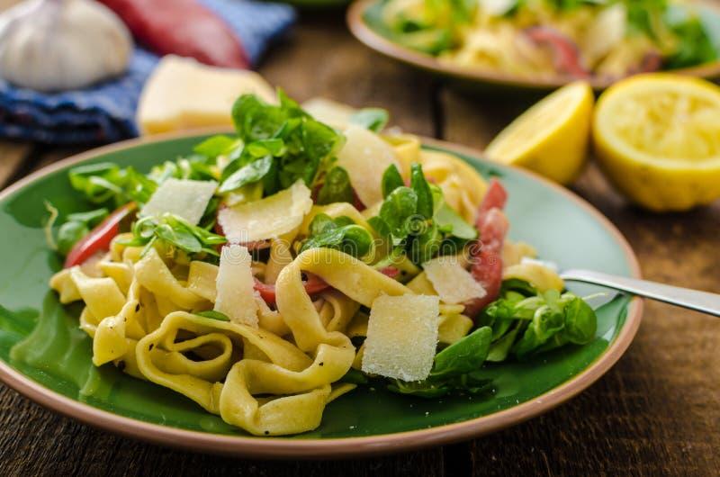 Tagliatelle用烟肉、大蒜和沙拉 免版税库存图片