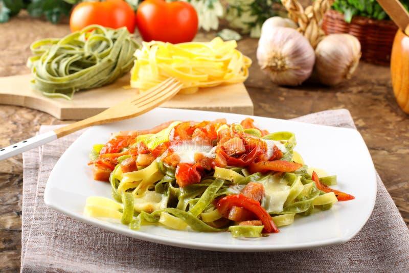 Tagliatelle用蕃茄、无盐干酪和烟肉 库存图片