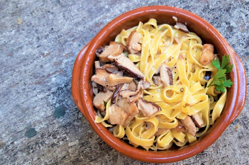 Tagliatelle用被收获的狂放的牛肝菌蕈类蘑菇和烟肉调味汁在木背景 免版税库存图片