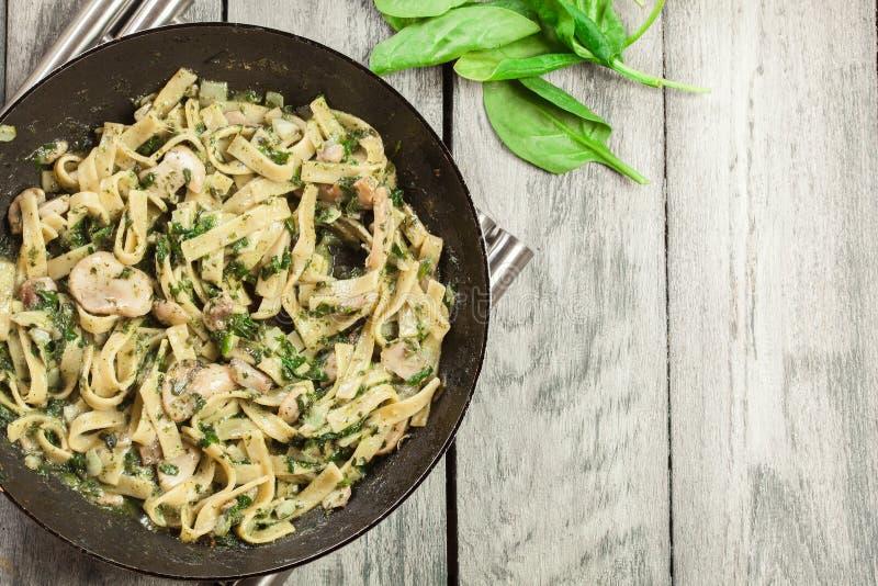 Tagliatelle面团用菠菜和蘑菇在平底锅 库存图片