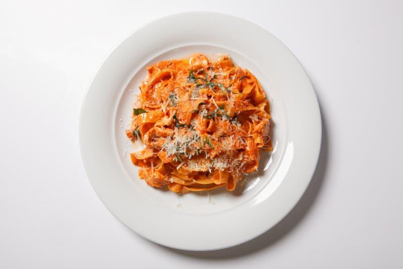 Tagliatelle макаронных изделий с томатом на белой предпосылке стоковое фото rf