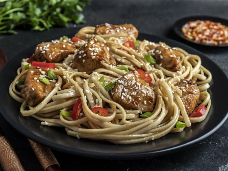 Tagliatelle asiatiche con il teriyaki del pollo, sesamo, fondo di pietra rustico closeup Tagliatelle cinesi/giapponesi fotografie stock