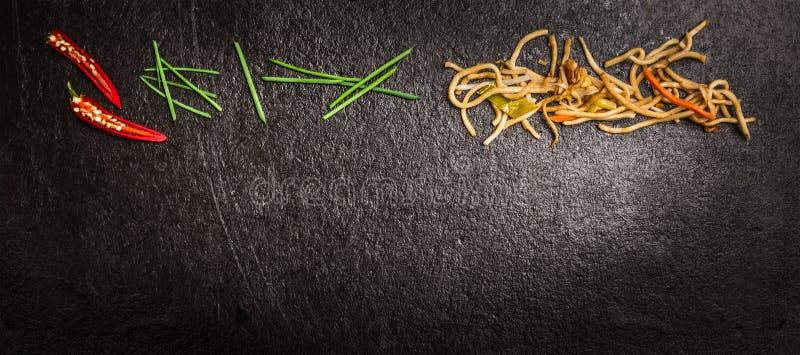 Tagliatelle asiatiche con la erba cipollina verde ed il peperoncino rosso rosso sul fondo scuro dell'ardesia, vista superiore, in immagini stock libere da diritti