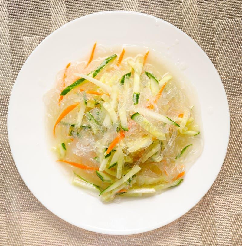 Tagliatelle cinesi con il cetriolo e la carota su un primo piano del piatto immagine stock