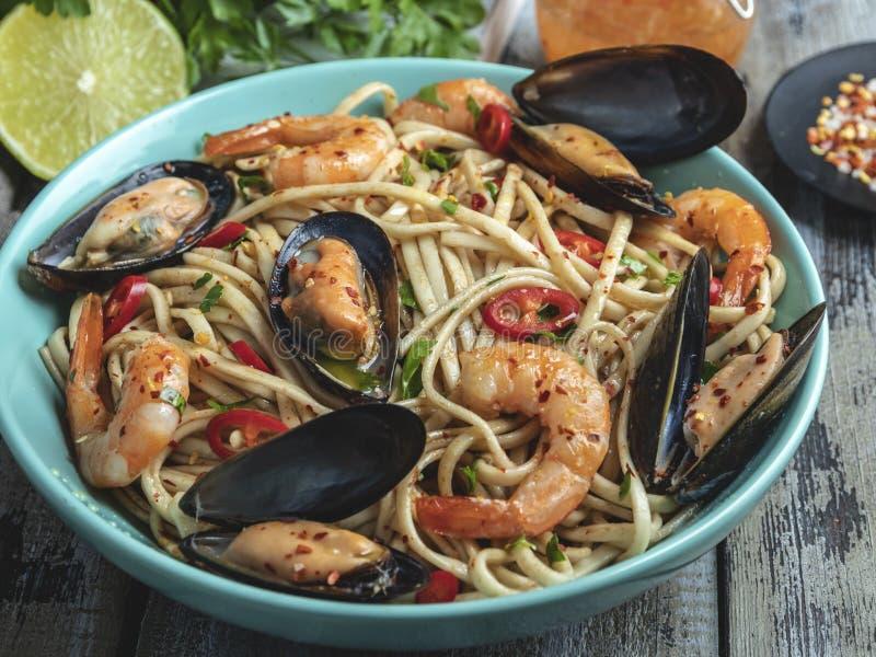 Tagliatelle con gamberetto e le cozze, spezia, sul piatto closeup Tagliatelle cinesi/giapponesi/asiatiche immagine stock libera da diritti
