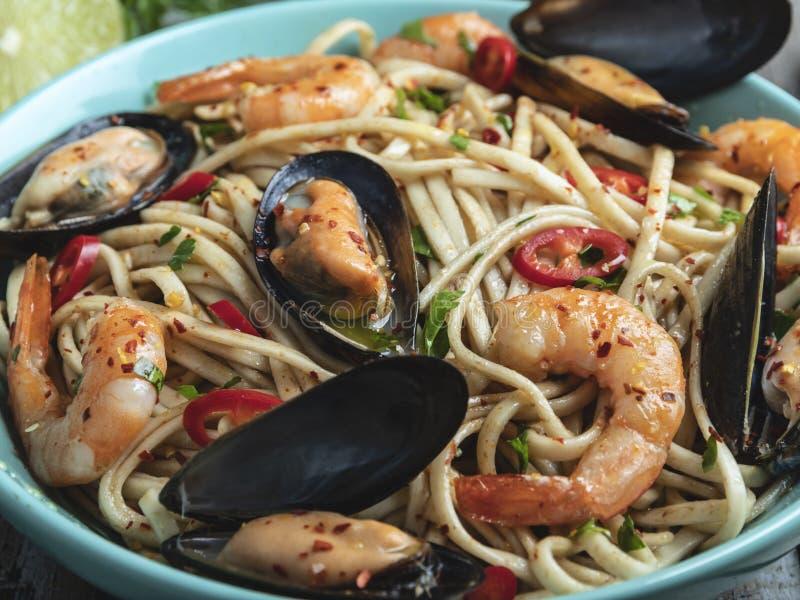 Tagliatelle con gamberetto e le cozze, spezia, sul piatto closeup Tagliatelle cinesi/giapponesi/asiatiche fotografia stock