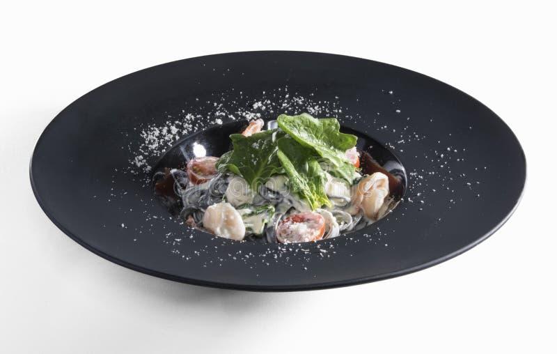 Tagliatelle con i gamberetti in piatto nero della stuoia isolato su bianco fotografia stock