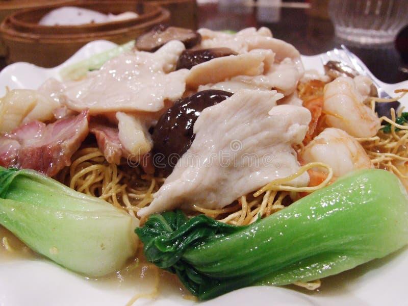 Tagliatelle croccanti dell'uovo dell'alimento cinese con carne di maiale, frutti di mare e cavolo cinese fotografia stock libera da diritti