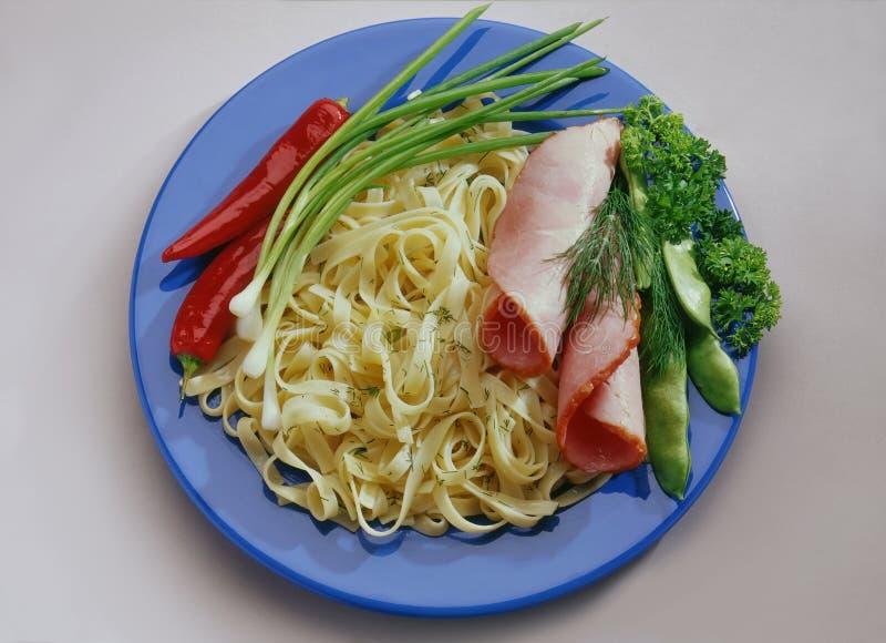 Tagliatelle del grano con il prosciutto tagliato, bacon su un piatto blu fotografia stock libera da diritti