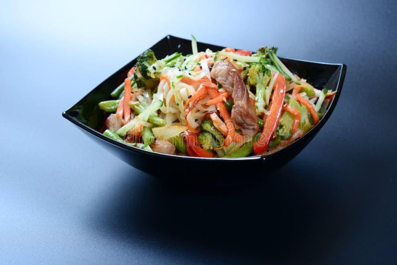 Tagliatelle del wok con i gamberetti, la carne e le verdure immagine stock