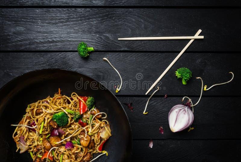 Tagliatelle della frittura di scalpore del Udon con il pollo e le verdure in pentola del wok su fondo di legno nero con i bastonc fotografia stock