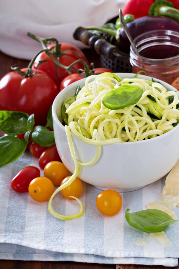 Tagliatelle dello zucchini in una ciotola con gli ortaggi freschi immagini stock