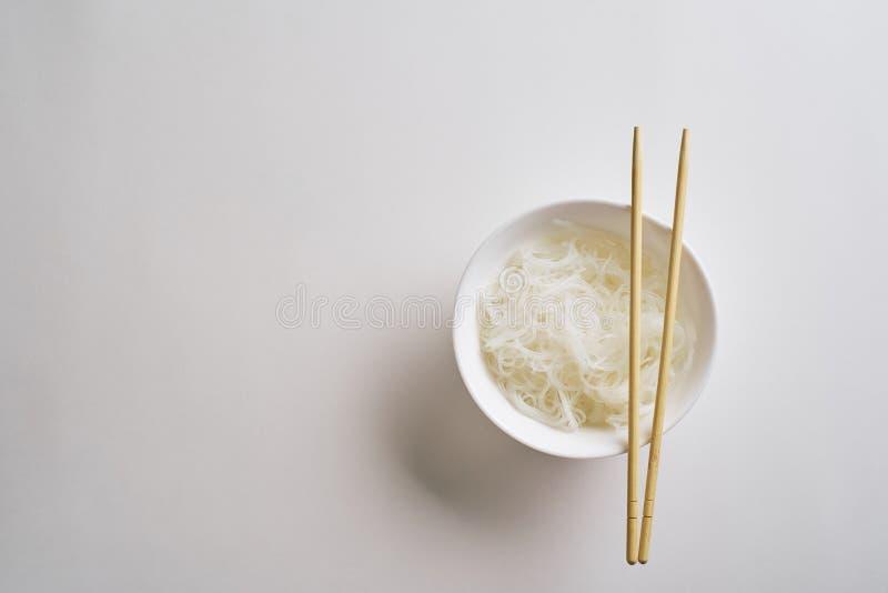 Tagliatelle di riso in un piatto con i bastoncini Tagliatelle di riso bollite in un piatto su un fondo bianco Vista superiore fotografia stock