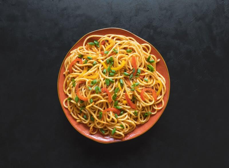 Tagliatelle di Schezwan con le verdure in un piatto su una tavola di legno Vista superiore Le tagliatelle di hakka è ricette tra  fotografia stock