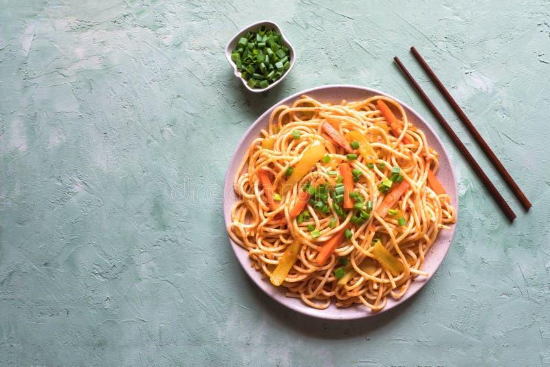 Tagliatelle di Schezwan con le verdure in un piatto su una tavola verde Vista superiore Le tagliatelle di hakka è ricette tra l'I fotografie stock libere da diritti