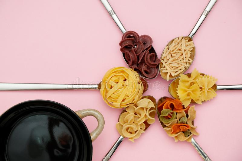 Tagliatelle, espaguetes e massa coloridos crus em colheres do metal, potenciômetro preto no fundo liso cor-de-rosa do raio fotos de stock royalty free