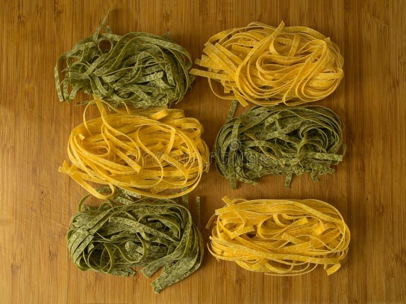 Tagliatelle of fetuccine gele en groene deegwaren op houten t stock afbeelding
