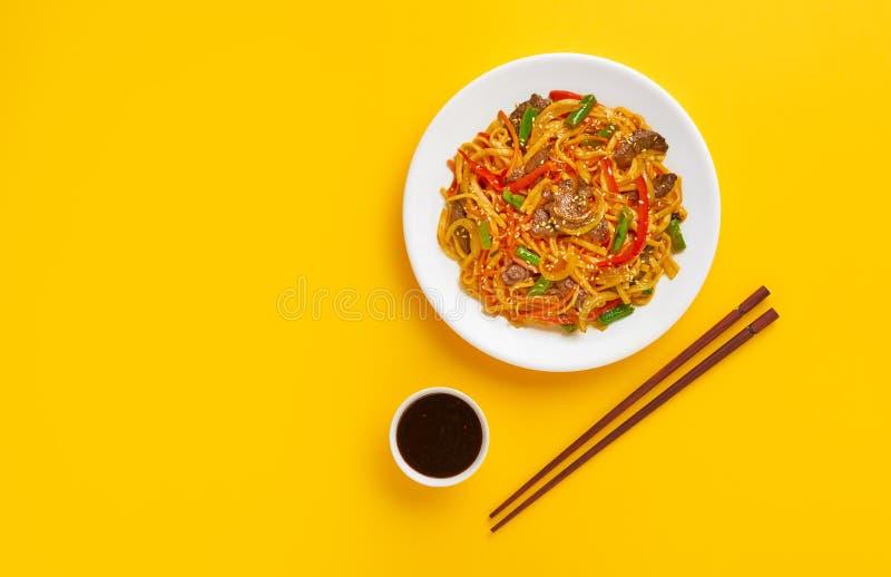 Tagliatelle fritte con manzo in un piatto su un fondo giallo Disposizione piana La vista dalla parte superiore immagini stock libere da diritti